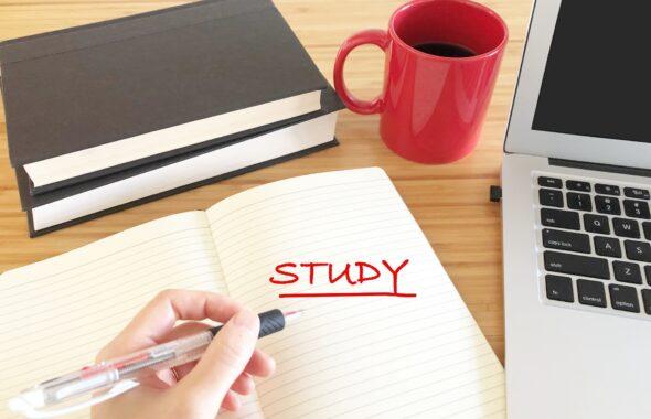 STUDYと赤ペンで書いている。パソコンとコーヒー